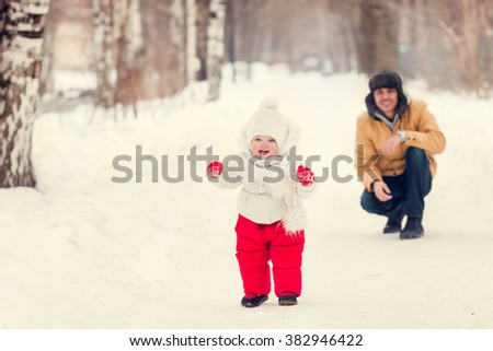 little girl making first steps behind dad outdoors in winter
