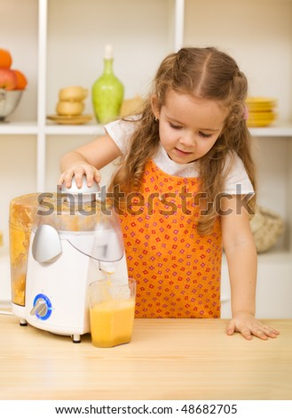 Little girl making fresh fruit juice with a kitchen appliance