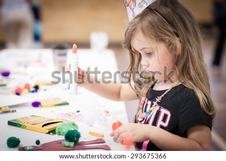 little girl making handcraft at a table at a kids party - stock photo