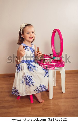 Little girl making makeup on the beauty table - stock photo