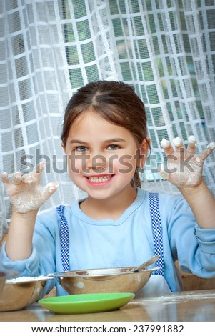 Little girl making pizza for lunch with her mother - stock photo