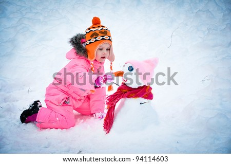 Little girl making snowman on a winter day - stock photo