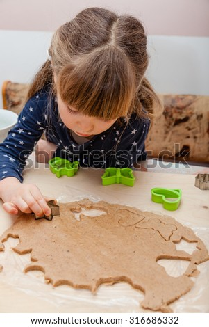 Little girl making stamp cookies on the raw dough in the kitchen. Family time. Kid helping concept. Fun to do house work. - stock photo
