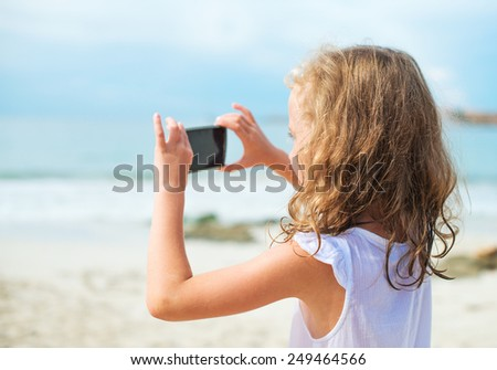 Little girl making video or photo with mobile phone. - stock photo