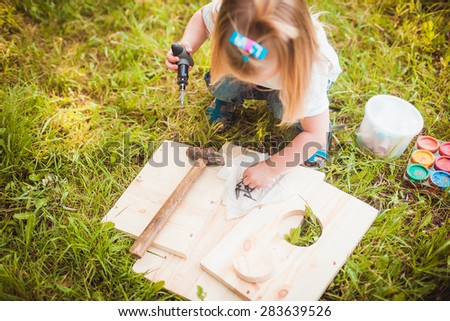 Little girl making Wooden birdhouse in summer green park - stock photo