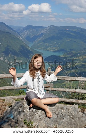 little girl meditating on a mountain top