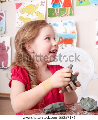 Little girl moulding from clay in play room. - stock photo