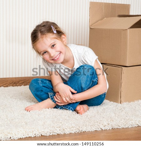 Little girl moving into new house, siting near cardboard box.  top view - stock photo