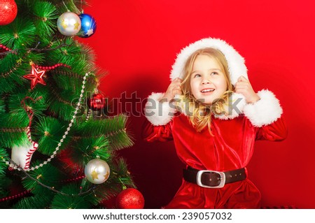Little girl near the Christmas tree with toys - stock photo