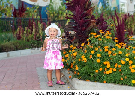 Little girl near the flower beds, a summer vacation, a walk in the park in the summer, flower bed in the form of an umbrella - stock photo