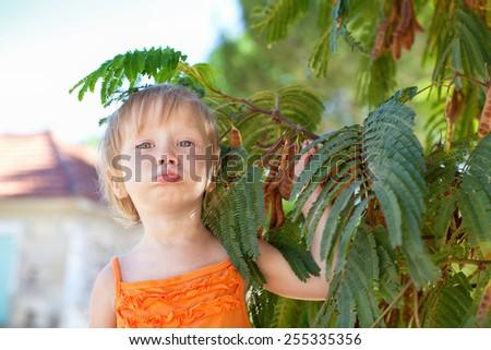 Little girl near the tree - stock photo