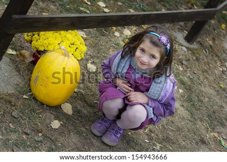 Little girl near wooden fence  with big pumpkin and flower - stock photo