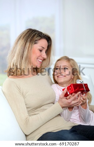 Little girl offering present to her mom - stock photo