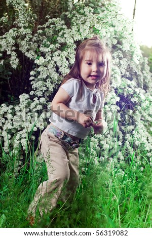 Little girl on a background a bush with white flowers