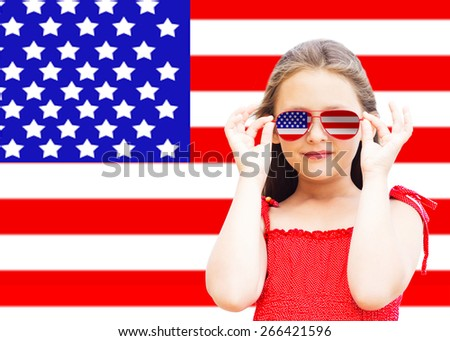 little girl on a background of the American flag - stock photo