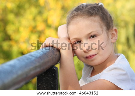 little girl on a bridge in early fall park is looking at camera - stock photo