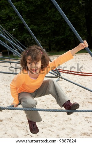 Little girl on a climbing frame at the playground