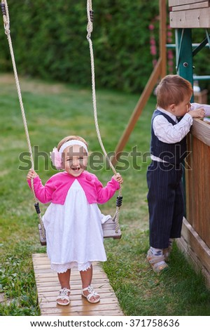 Little girl on a playground riding on a swing in summer. - stock photo