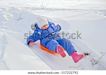Little girl on a sled sliding down a hill in the snow in winter