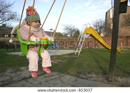 Little Girl on a swing at the playground in the winter time.