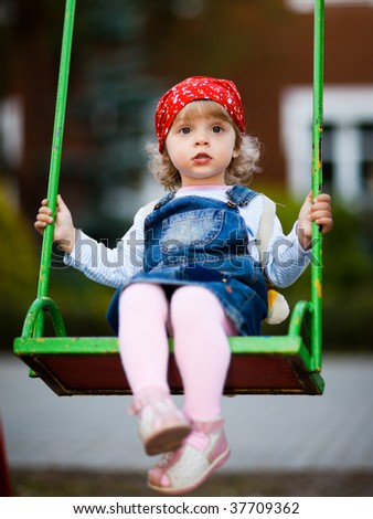 Little girl on a swing - shallow DOF - stock photo