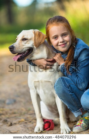 Little girl on a walk with the dog.