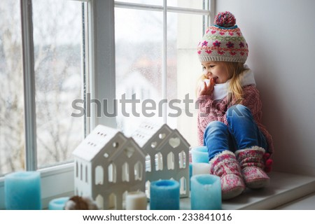 little girl on a window sill looks at the street - stock photo