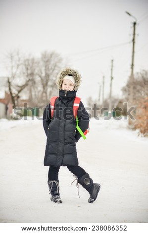 Little girl on a winter day with a school backpack - stock photo