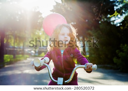 Little girl on bicycle in the park, soft focus in sun rays. - stock photo