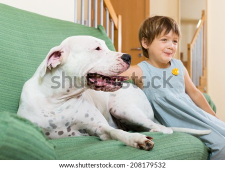 little girl on couch with dogo Argentino (focus on dog)