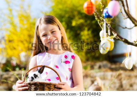 Little girl on Easter egg hunt in the spring, an Easter bunny is sitting in a basket - stock photo