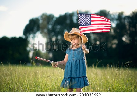 Little girl on  field with American flag and toy gun.