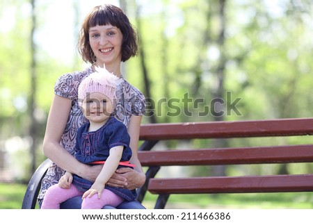 little girl on hands at mum - stock photo
