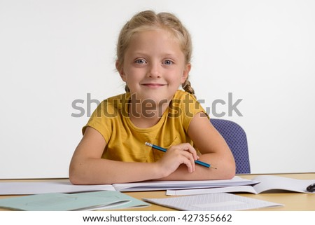 Little girl on her workplace with a pencil in her hand. Young princess looks right in the camera with beautiful big blue eyes and has fantastic childish smile.  - stock photo