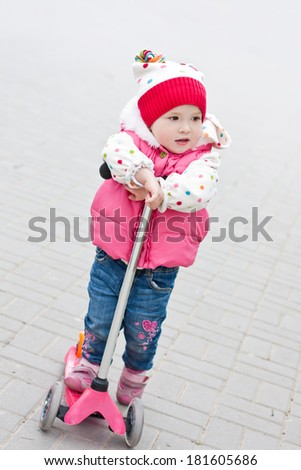 little girl on scooter in the park - stock photo