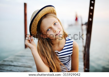 little girl on sea background. little girl in a hat - stock photo