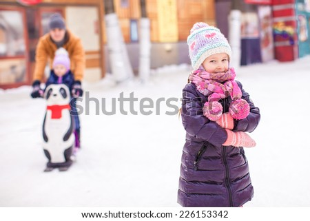 Little girl on skating rink, dad with little sister in the background - stock photo