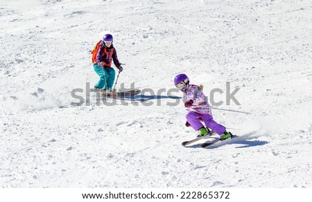 Little girl on skis in soft snow under the care of my mother on a sunny day in the mountains - stock photo