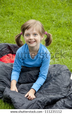 little girl on sleeping bag - camping concept - stock photo