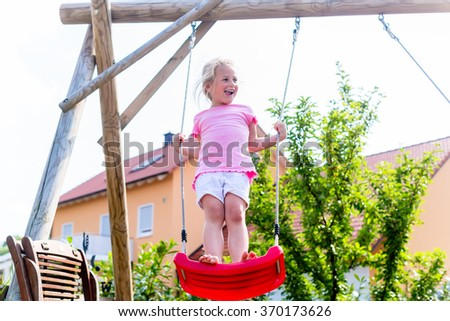 Little girl on swing in front of house - stock photo