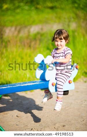 Little Girl on swings summer time outdoors - stock photo