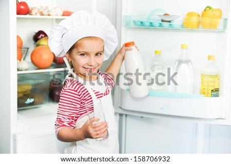 little girl on the background of the fridge drinking milk - stock photo