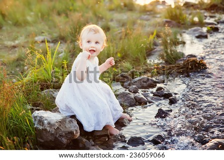 little girl on the bank of the river - stock photo