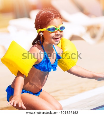 Little girl on the beach, having fun near swimming pool and preparing to jump into the water, spending summer holidays on beach resort - stock photo
