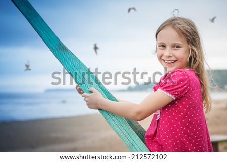 Little girl on the beach on a swing. - stock photo