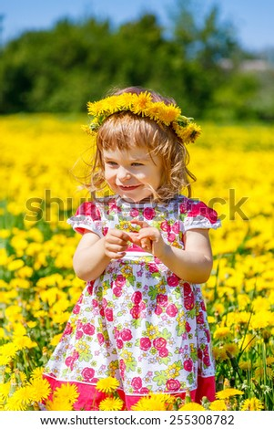 Little girl on the blooming dandelions field - stock photo