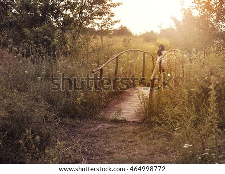 little girl on the bridge, running to the sunset on the field with grass.