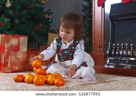 Little girl on the carpet in the room with Christmas decorations