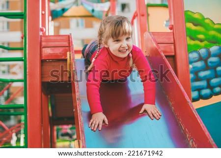 Little girl on the playground descending on a slide - stock photo