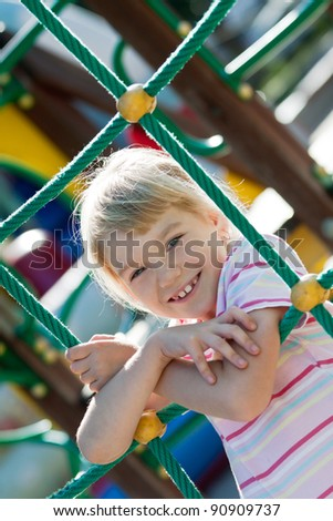 Little girl on the playground having fun at summer time. - stock photo